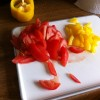 Red and yellow peppers sliced on a white chopping board