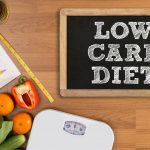 LOW CARB DIET Fitness and weight loss concept dumbbells white scale fruit and tape measure on a wooden table top view free copy space