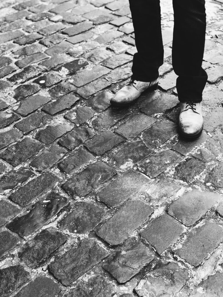 Man in shoes standing on cobblestones